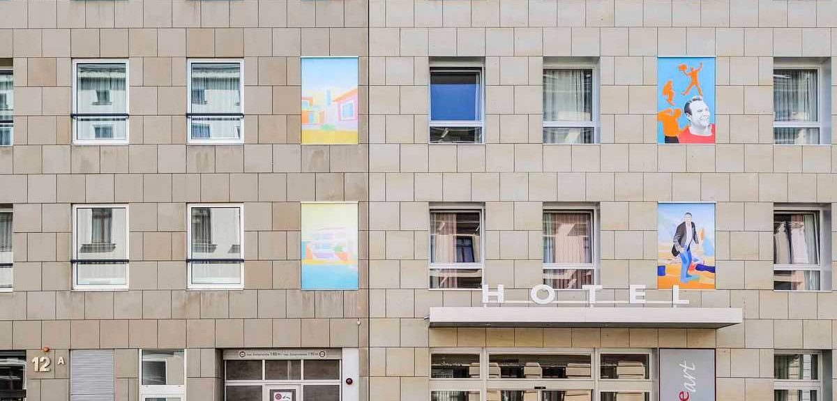 Beige, tiled hotel exterior with multicolored murals and Amberline windows