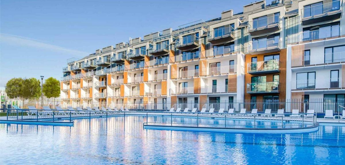 White and yellow poolside residential hotel with balconies and Amberline windows