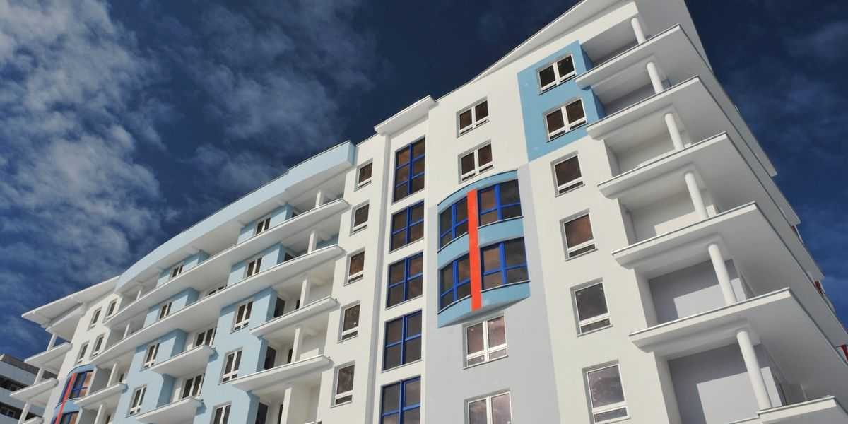 Multifamily apartment development with white, blue, and gray exterior and Amberline windows.